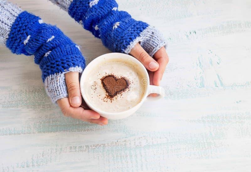 拿着与舒适羊毛手取暖器的咖啡拿铁 免版税库存照片