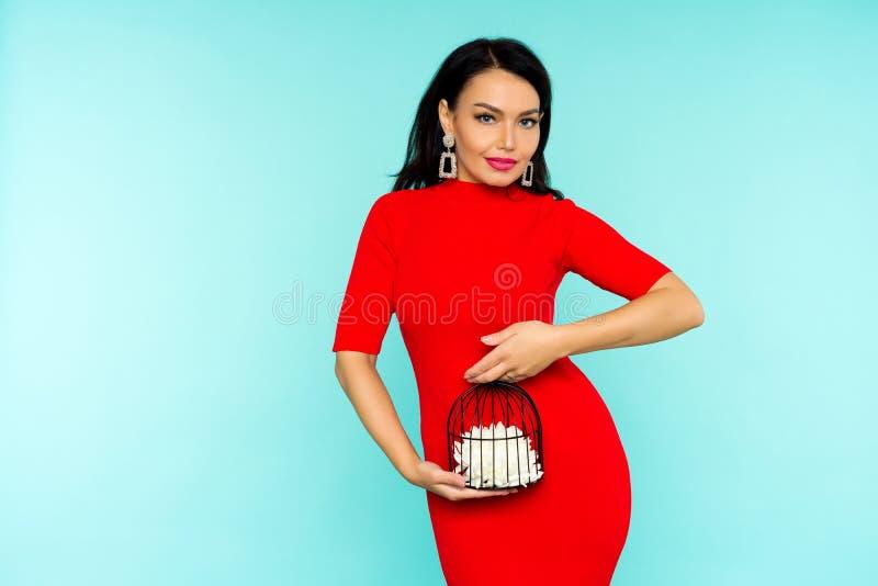 拿着与花里面的红色礼服的美丽的性感的深色的妇女一个鸟笼在蓝色背景 图库摄影