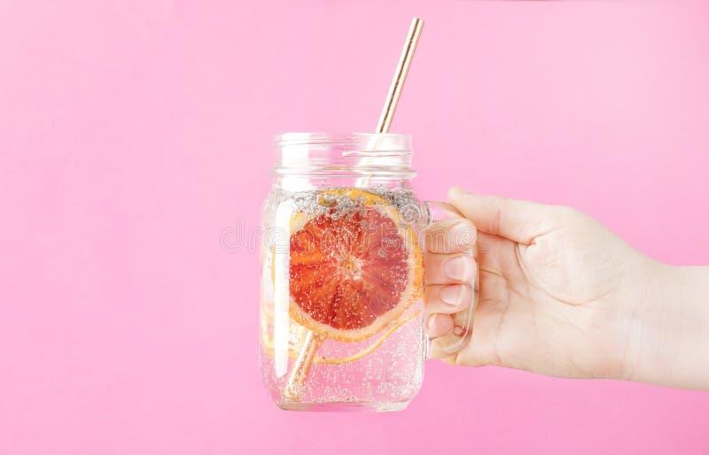 拿着与苏打、橙色切片和chia种子的女性手夏天饮料在桃红色背景,选择聚焦的玻璃瓶子 免版税库存照片