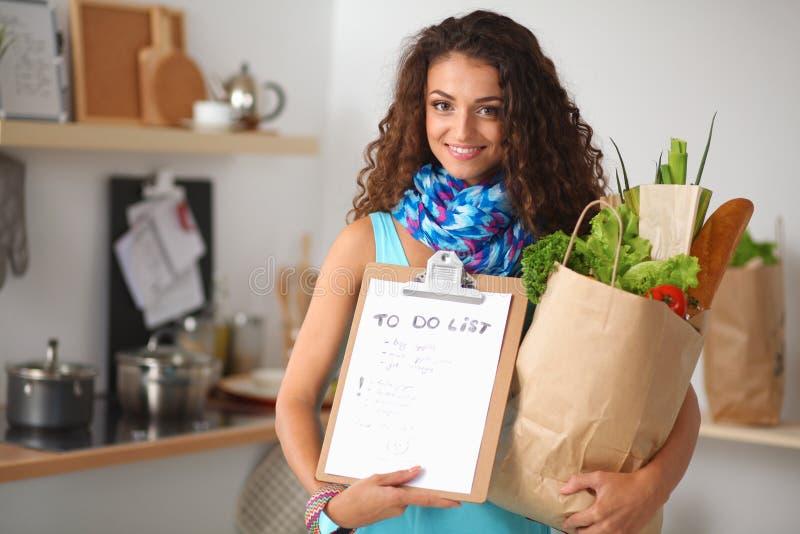 拿着与菜的少妇买菜袋子站立在厨房里 免版税库存图片