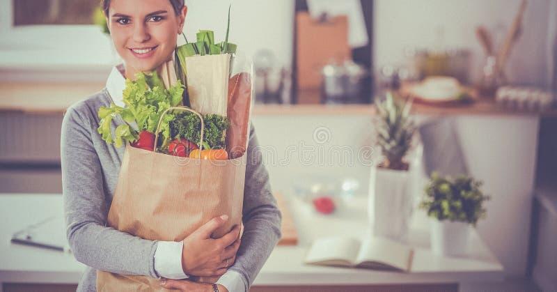 拿着与菜的少妇买菜袋子站立在厨房里 免版税图库摄影