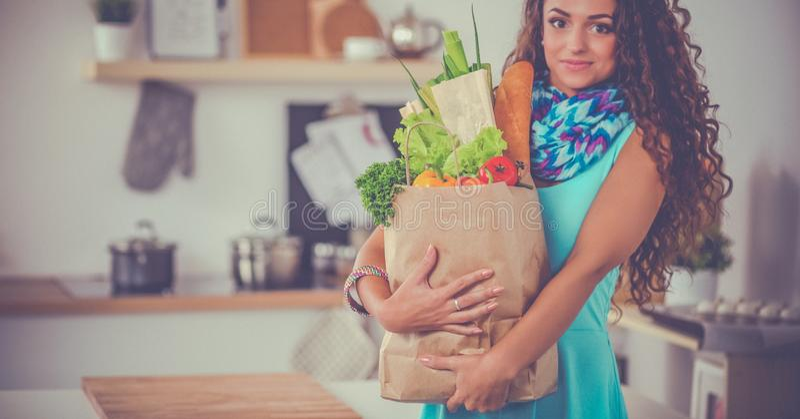 拿着与菜的少妇买菜袋子站立在厨房里 图库摄影