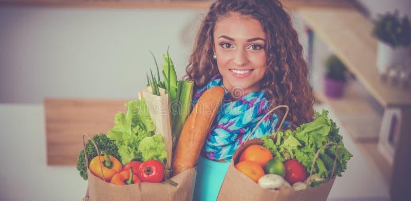 拿着与菜的少妇买菜袋子站立在厨房里 库存照片