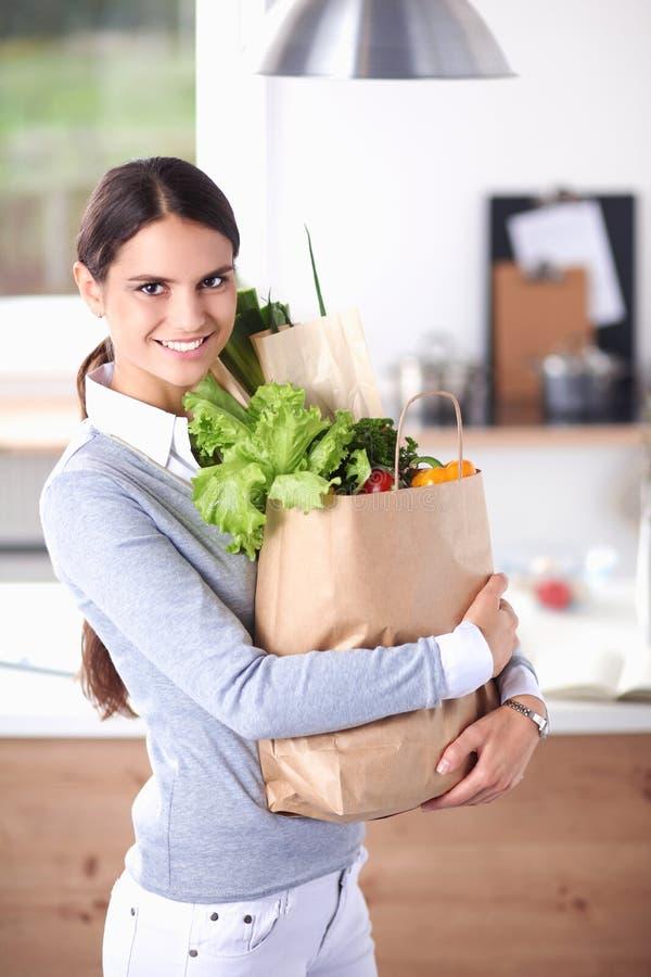 拿着与菜的少妇买菜袋子 站立在厨房里 免版税库存照片