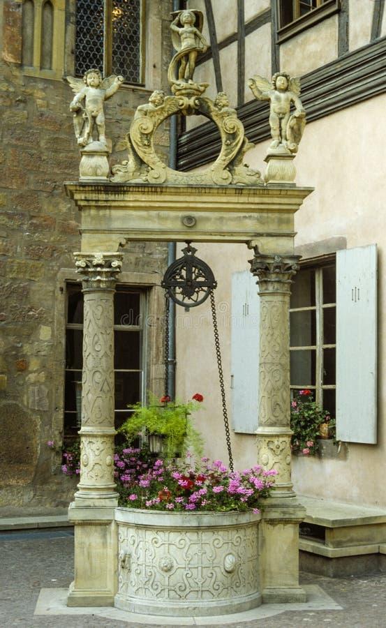 拿着与被雕刻的天使的一个小石喷泉桃红色花站立在上面 库存照片