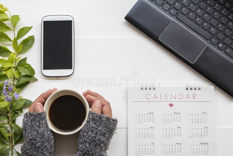拿着与设备办公室的妇女的手咖啡企业工作的 免版税图库摄影
