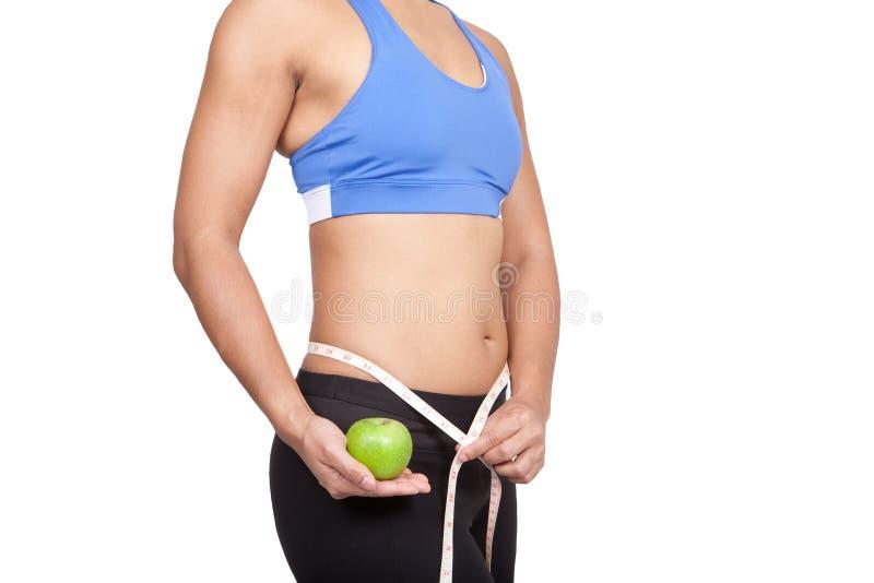 拿着与评定的磁带的妇女绿色苹果。 免版税库存图片