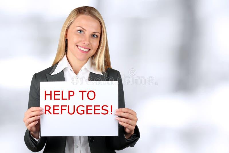 拿着与词的微笑的妇女一副白色横幅帮助给难民 免版税库存图片