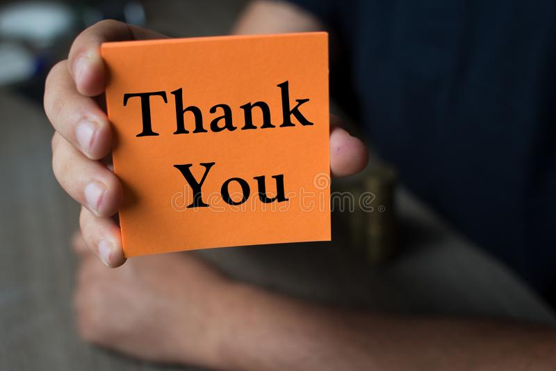 拿着与词的手橙色纸感谢您-事务 库存图片