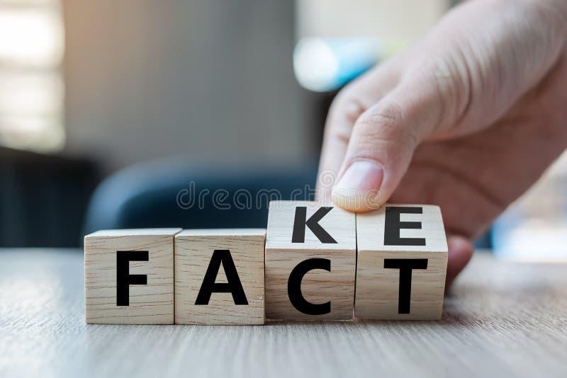 拿着与轻碰的商人手木立方体在块伪造品对在桌背景的事实词 新闻、解答和事务 免版税库存图片