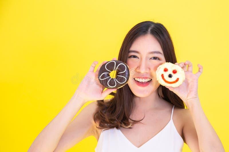 拿着与逗人喜爱的微笑的表示的可爱的亚裔妇女两个油炸圈饼在黄色背景 图库摄影