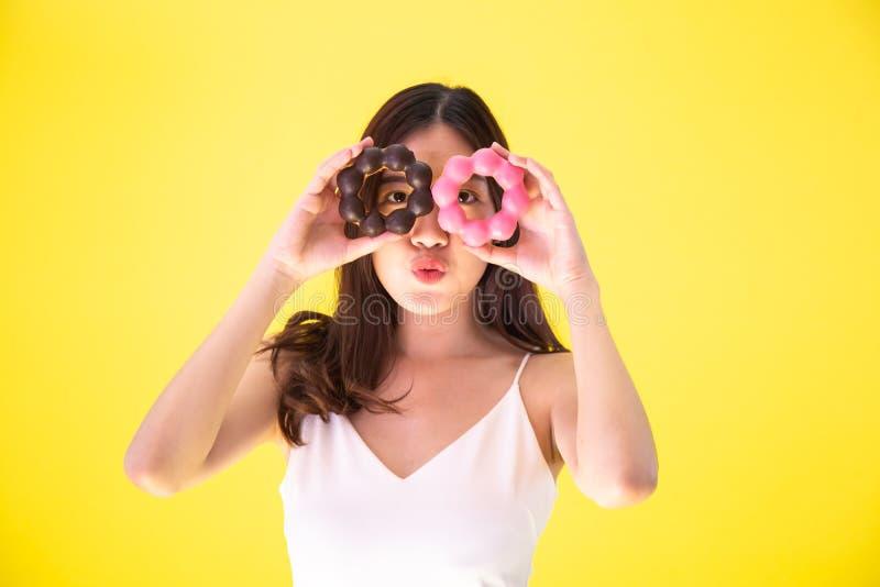 拿着与逗人喜爱的微笑的表示的可爱的亚裔妇女两个油炸圈饼在黄色背景 库存图片