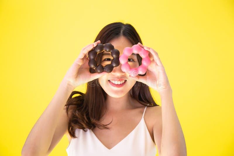 拿着与逗人喜爱的微笑的expr的可爱的亚裔妇女两个油炸圈饼 免版税库存照片
