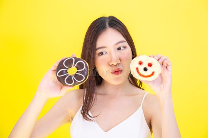 拿着与逗人喜爱的表示的可爱的亚裔妇女两个油炸圈饼在黄色背景 免版税库存图片