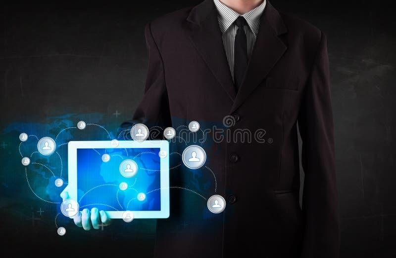 拿着与通讯技术concep的年轻人talbet 图库摄影