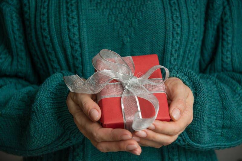 拿着与银色丝带的女性手圣诞节红色giftbox 节假日 节礼日 库存照片