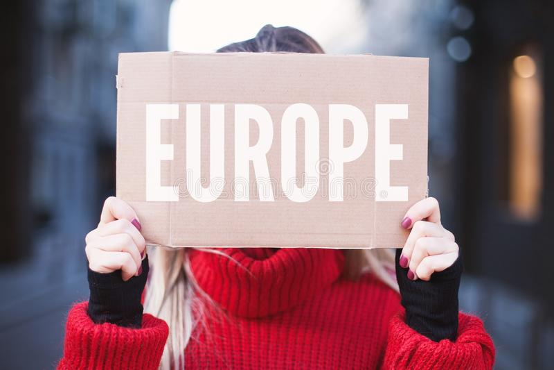 拿着与题字'欧洲的'女生一个标志 搭车在欧洲附近 免版税图库摄影