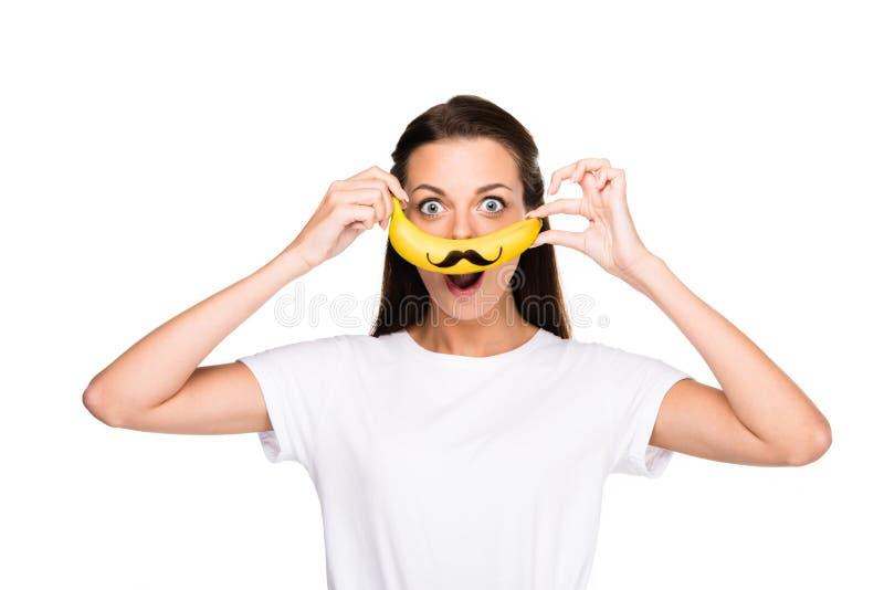 拿着与髭标志的激动的妇女画象新鲜的香蕉 库存照片
