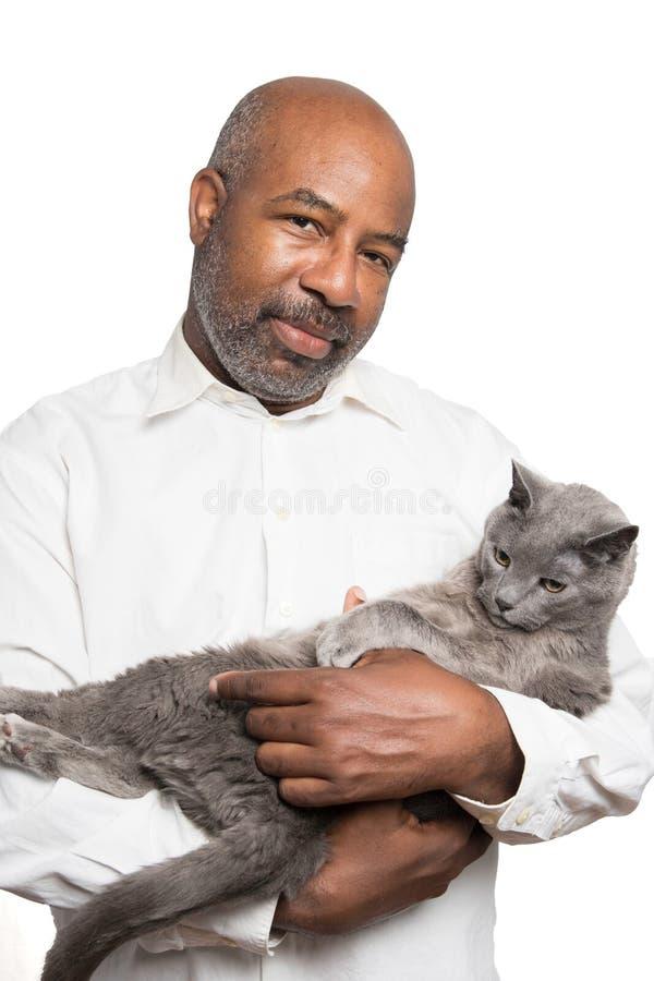 拿着与黄色眼睛的一个有胡子的大胆的非裔美国人的人的画象一只灰色猫在与拷贝空间区域的白色背景 免版税库存照片