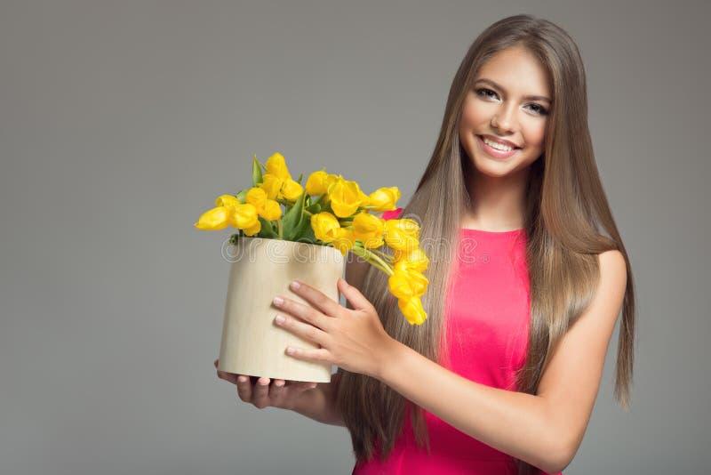 拿着与黄色郁金香的年轻愉快的妇女篮子 免版税库存图片