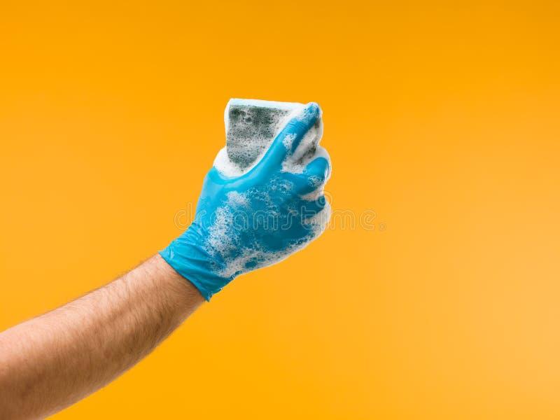 拿着与洗涤剂的手海绵 库存图片