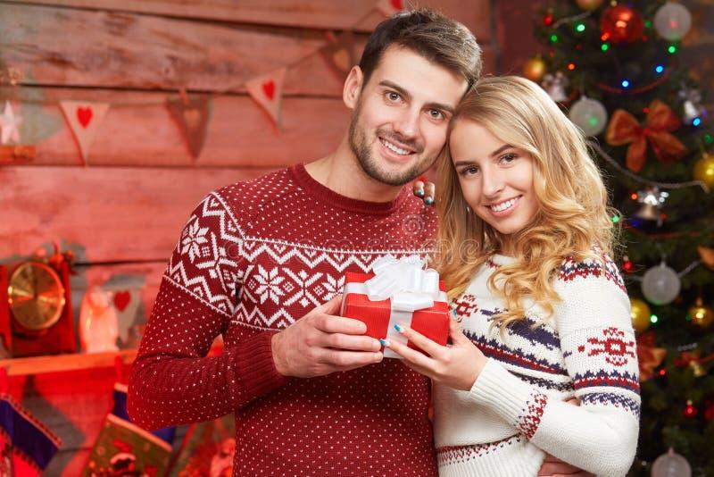 拿着与他的女朋友的愉快的年轻人圣诞节礼物 免版税库存图片
