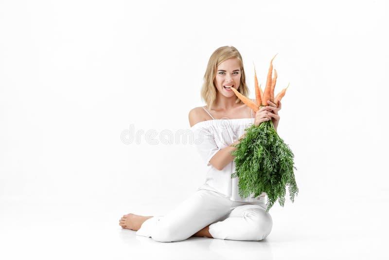 拿着与绿色的美丽的白肤金发的妇女新鲜的红萝卜在白色背景离开 饮食健康 库存照片