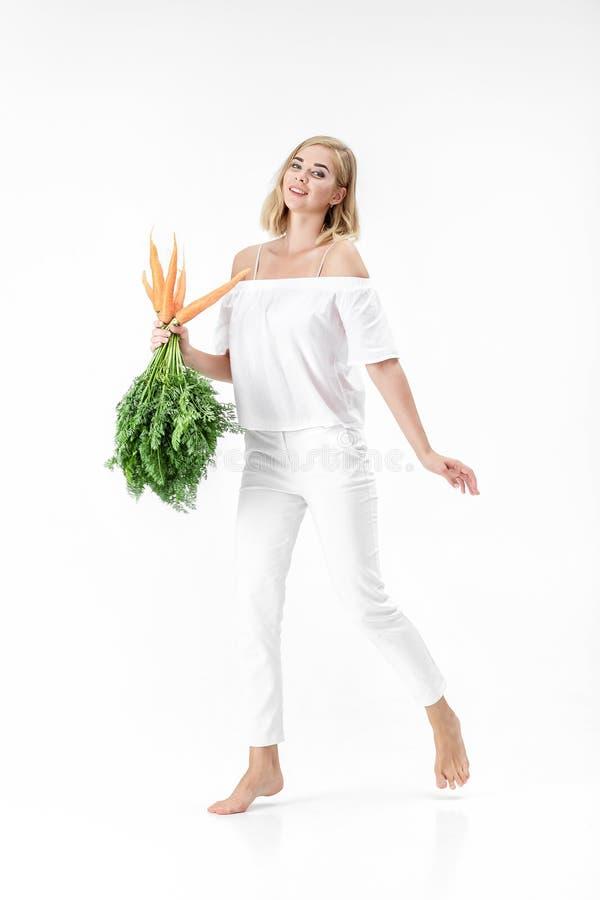 拿着与绿色的美丽的白肤金发的妇女新鲜的红萝卜在白色背景离开 饮食健康 免版税库存图片