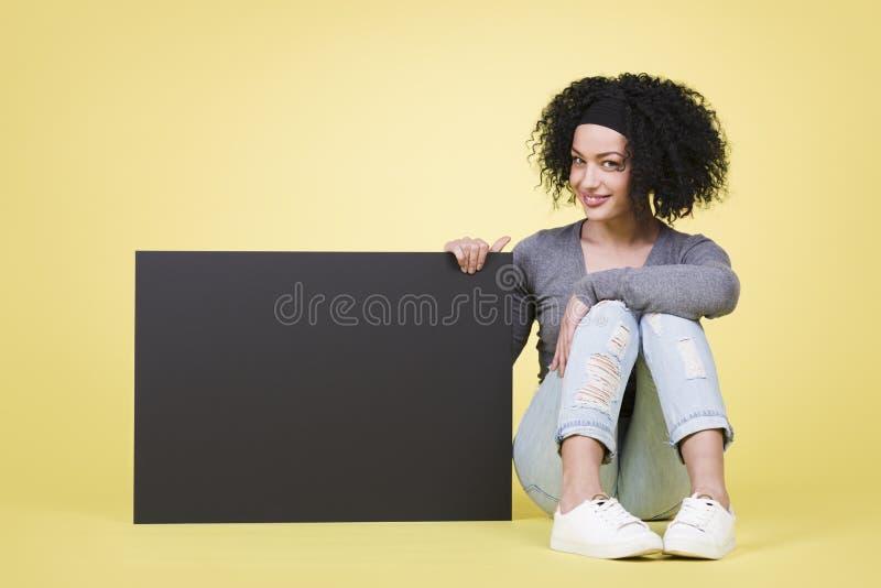 拿着与copyspace的愉快的女孩一个空白的标志 库存图片