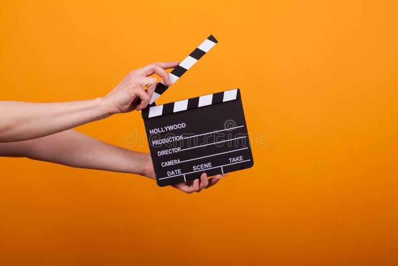 拿着专业影片板岩,电影拍板的妇女在黄色背景的演播室 免版税库存图片