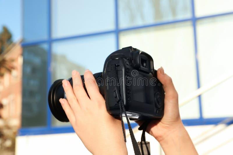 拿着专业照相机的女性摄影师户外 库存照片