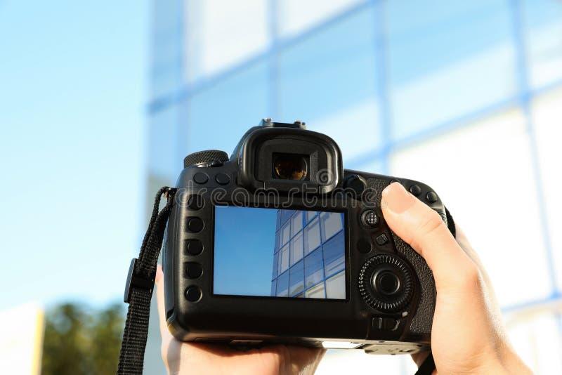 拿着专业照相机的女性摄影师 免版税库存图片