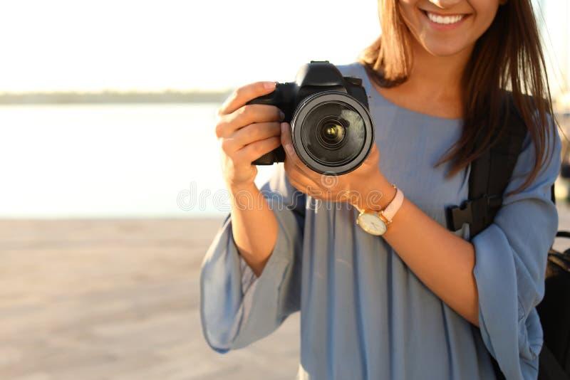 拿着专业照相机的年轻女性摄影师在码头,特写镜头 免版税图库摄影