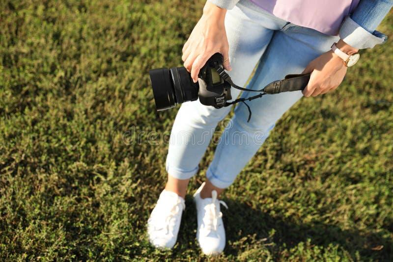 拿着专业照相机的年轻女性摄影师户外 免版税库存照片
