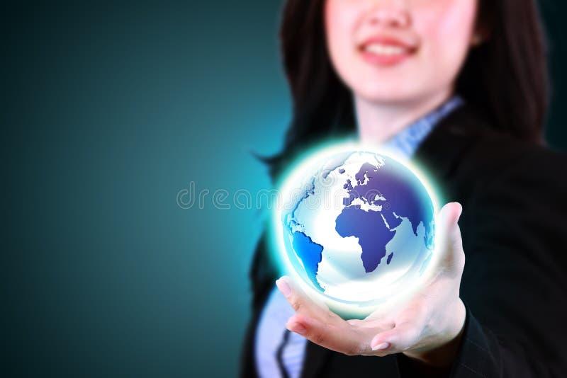 拿着世界的女商人 免版税库存照片