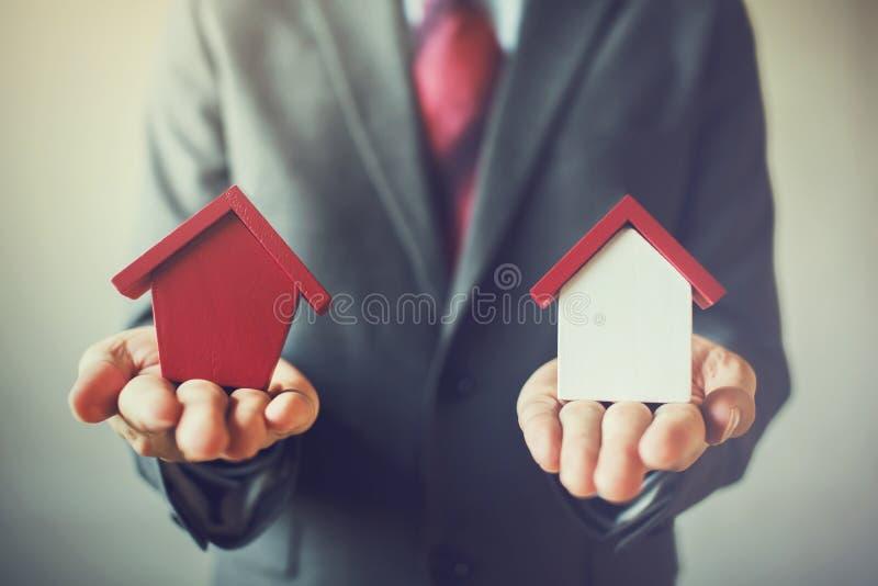 拿着两个房子的商人,并且不可能决定选择r 免版税图库摄影