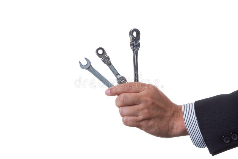拿着两个棘轮套筒扳手和开口扳手在他的手上的技工工程师 库存图片