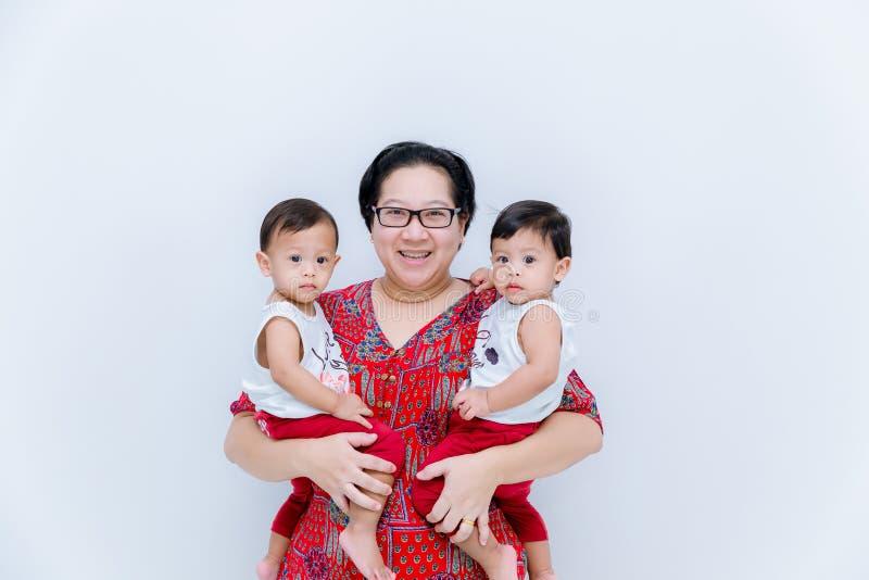 拿着两个男婴的母亲 伟大的幸福,有两孪生婴孩的愉快的年轻妈妈 拿着她的小tw的年轻母亲画象 免版税库存图片