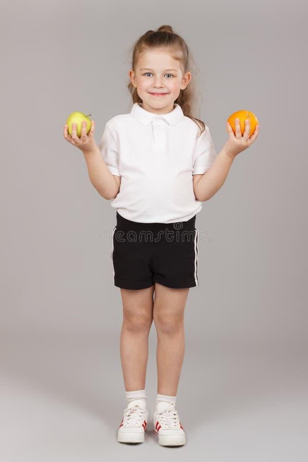 拿着两个苹果的小女孩 免版税库存图片