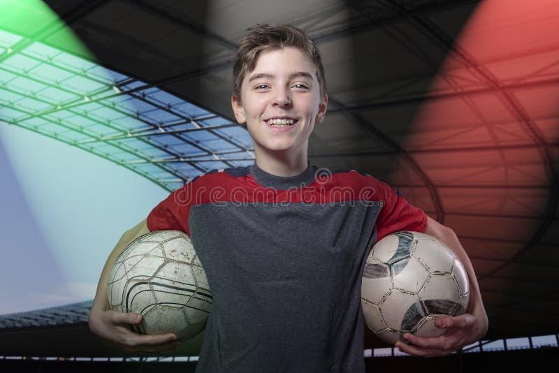 拿着两个足球的骄傲,微笑的十几岁的男孩 免版税库存图片