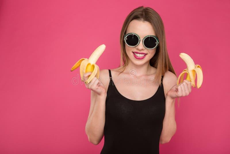 拿着两个香蕉的正面可爱的少妇画象  免版税库存照片