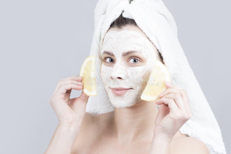 拿着两切片柠檬的秀丽少妇witn面部crem面具 护肤概念 免版税图库摄影