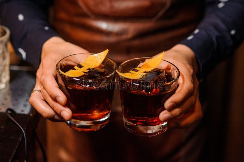 拿着两块玻璃的男服务员用酒精饮料填装了 免版税图库摄影