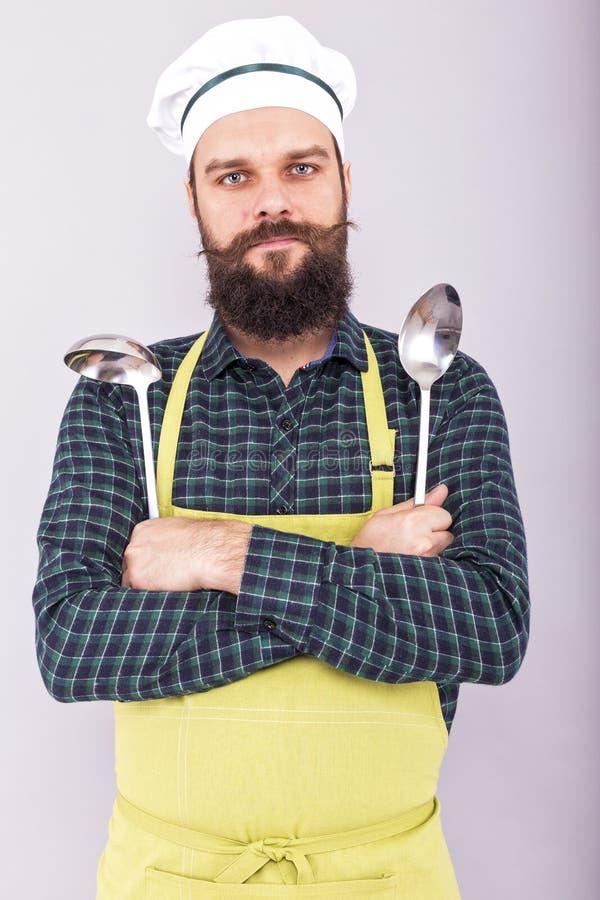 拿着两大厨房器物,小伙子的一位有胡子的厨师的画象 免版税库存图片