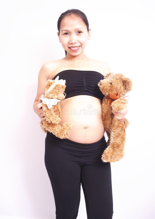 拿着两女用连杉衬裤的怀孕的愉快的小姐涉及白色背景 图库摄影