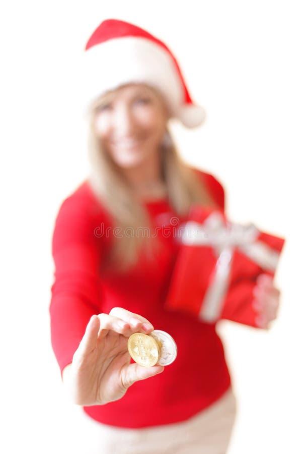拿着两枚cryptocurrency硬币的微笑的妇女 图库摄影