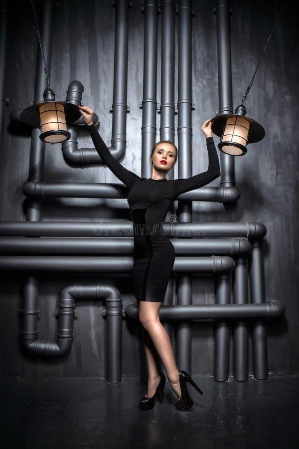 拿着两盏减速火箭的灯的黑礼服的年轻,美丽的妇女 库存照片