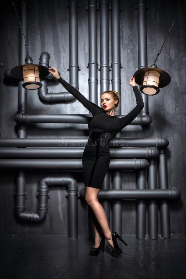 拿着两盏减速火箭的灯的黑礼服的年轻,美丽的妇女 免版税图库摄影