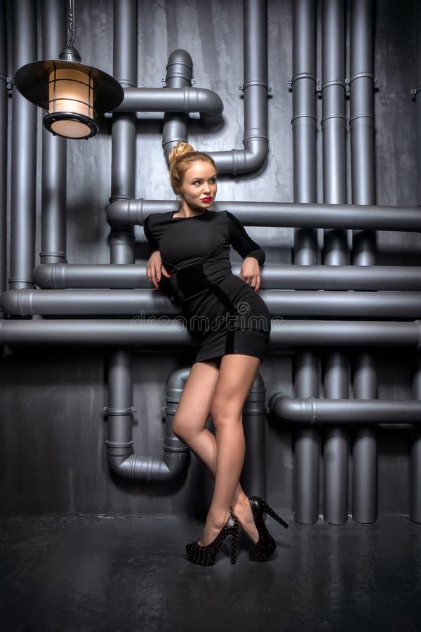 拿着两盏减速火箭的灯的黑礼服的年轻,美丽的妇女 免版税库存图片