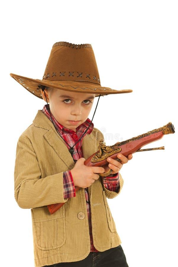 拿着严重的玩具武器的牛仔 免版税库存图片